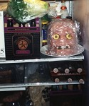 A plastic skull covered with Jello and cold cuts wrapped with plastic wrap